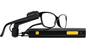 Imagen del sistema Orcam. En ella se observa la microcámara, que en este caso ya está acoplada a la patilla de unas gafas normales, y la unidad de procesamiento que va unida por medio de un cable a la microcámara