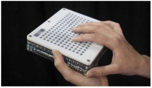 Fotografía de una tableta táctil blanca, de 12 x 15 centímetros de superficie, y 1 centímetro de ancho.  Sostenida entre las manos de un usuario, una mano debajo, que la sujeta, y la otra encima, y apoyando, ligeramente, las yemas de los dedos sobre los botones que formarán el relieve, y que le permitirán percibir la información gráfica del entorno.