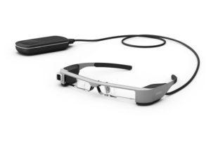 Imagen de las gafas de realidad aumentada usadas por el sistema Retiplus, las EPSON Moverio BT-300. En ella se observa estas gafas, con sus cristales totalmente transparentes, la microcámara incorporada en la patilla derecha, y el mando a distancia