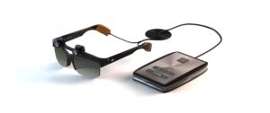 Imagen de las gafas Eyesynth, concretamente de uno de los prototipos previos al diseño definitivo. En ella se observa las gafas con sus dos microcámaras 3D incorporadas en la montura encima de cada uno de los cristales y la unidad de procesamiento, que va conectada a las gafas por medio de un cable. Este cable se bifurca en dos, yendo cada uno de ellos a cada una de las patillas de las gafas. En este prototipo no se aprecian los auriculares de transmisión ósea