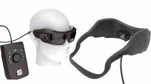 Imagen del sistema IRIS II mostrando una cabeza de maniquí portando las gafas con su microcámara, a su lado el procesador que transmite la señal al microchip, y una vista trasera de las gafas donde se aprecia la sujeción a la cabeza y la microcámara incorporada en su parte izquierda.