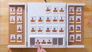 Fotografía del tablero, en forma de tríptico, permitiendo cerrarlo y hacerlo transportable (50 X 40 cm aproximadamente la parte central). Se visualizan todas las fichas (4 X 3 cm. aproximadamente cada una), una ficha por cada letra del alfabeto. Cada ficha tiene impresa, en la parte superior, la letra en tinta, y en la inferior, grabada en Braille. La parte de abajo del tablero contiene la regleta o línea, con los huecos en forma de cajetín, en el que se introducen las letras , que mediante el archivo audio mencionará la letra escogida.