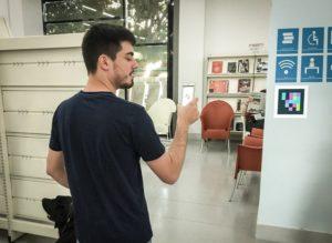 Imágen de un usuario ciego en un espacio interior elevando  su móvil unos dos metros, aproximadamente, para rastrear la etiqueta identificativa que se halla pegada en la pared de la entrada a un espacio contiguo, junto con otras etiquetas en tinta para usuarios videntes.