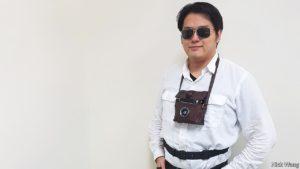 imagen de una persona en posición estática de perfil con una funda protectora de 15  por 15 cm colgada en el cuello que porta una cámara fotográfica y con un cinturón con motores vibradores de 2 cm en su cintura.