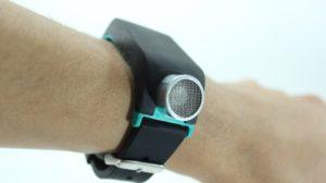 Imagen en la que se observa la pulsera Sunu Band en la muñeca de una persona. La pulsera es de color negro, a excepción de su parte inferior, que en este modelo es de color azul claro, y del sensor de ultrasonido que es plateado.