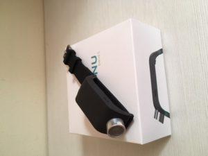 Imagen en la que se observa la pulsera Sunu Band encima de su caja. La pulsera es completamente de color negro, a excepción del sensor ultrasónico y de la hebilla, que son plateados.