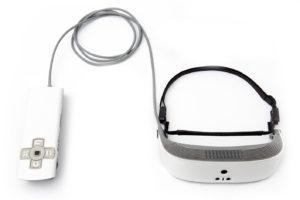 Imagen en la que se observa las smartglasses eSight 3 y su procesador de control remoto, el cual va conectado a las gafas por medio de un cable. En este modelo, ambos componentes son de color blanco. Las gafas, de apariencia futurista a la vez que elegante, no tienen cristales transparentes, sino que son totalmente opacas.