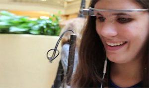 Imagen de una joven con las gafas de AIRA en cuya montura se aprecia una doble patilla en su parte derecha, sirviendo de soporte, tanto a la mini-cámara como al módulo de transmisión Wi-FI. Su gesto es el de estar enfocando a un objeto o a una escena.