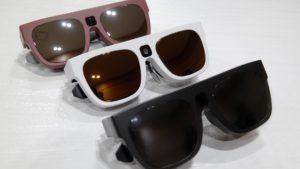 Imagen de las gafas Relúmino en la que aparecen tres modelos de distintos colores: uno rojo, otro blanco y otro negro. Visualmente se asemejan mucho a unas gafas de sol clásicas con patillas anchas, con la salvedad de que en el puente se aprecia el orificio de la Cámara de video.