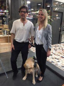 Imagen en la que se puede observar ,de izquierda a derecha, a Enrique Varela, su perro guía Balú y a Rotem Geslevich, con el fondo del hall del Impact Hub Alameda. Enrique lleva unas gafas de sol con OrCam MyEye 2.0.