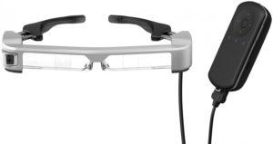 Imagen de las smartglasses de realidad aumentada empleadas en el sistema Retiplus, las EPSON Moverio BT-350. Las gafas, de aspecto futurista pero sin llegar a la extravagancia, son de color gris y negro, tienen unas lentes totalmente transparentes, una microcámara incorporada en la patilla derecha y sus patillas son graduables para poder adaptarse a los distintos tamaños de cabeza. En la imagen también aparece El controlador que permite interactuar con el sistema. Éste es de color negro, va unido por medio de un cable a las gafas, y en su interior se encuentran la batería y el procesador.