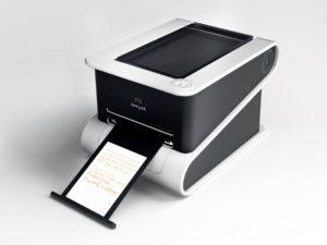 Imagen del prototipo de la impresora multifunción b.my.jet. Es de color negro y gris, y aparentemente es muy similar a cualquier impresora multifunción de escritorio del mercado, con el escáner en la parte superior y con la consiguiente bandeja para los documentos impresos.
