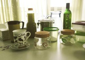 Imagen en la que se observa una mesa con un conjunto de etiquetas pequeñas en blanco de NaviLens y varios objetos domésticos como botes de plástico, Tuppers y botellas.