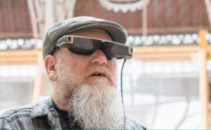 Imagen en la que se observa un hombre llevando las smartglasses para baja visión OxSight Prism. Las gafas son de color negro y gris metalizado, llevan la cámara integrada en la patilla derecha y engloban por completo a los ojos, ciñéndose por completo a la forma de la cara, sin dejar aberturas en los laterales. Los cristales son oscuros pero transparentes, cuentan en su interior con unas pantallas micro-OLED también transparentes, y de la patilla izquierda surge un cable que, aunque no se aprecia en la imagen, va a un controlador/procesador de color negro que incluye la unidad de procesamiento del sistema, la batería y los controles de las distintas funciones del equipo. Las gafas tienen una estética futurista pero sin llegar a ser muy aparatosas.