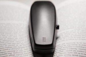 Imagen: Dispositivo BraiBook sobre un libro impreso en tinta, en la imagen se ve el dispositivo de frente, la celdilla con los puntos en braille y el joystick.