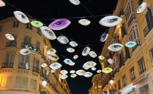 Imágen nocturna de la emblemática calle Larios de Málaga, adornada de carnaval, con luces que dibujan ojos de múltiples colores.